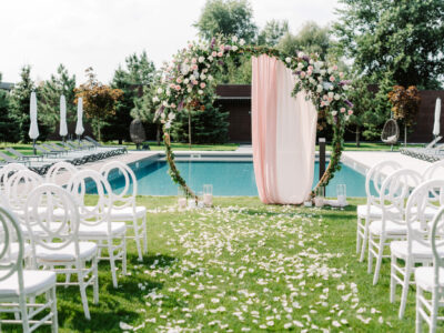 A stylish round green arch for a wedding ceremony on the lawn near the pool. Modern decoration of the place for the open-air marriage ceremony