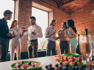 Company of six nice trendy attractive pretty elegant cheerful glad positive caucasian guys ladies pairs pal having fun luncheon brunch best tradition table buffet snack in industrial loft interior room.
