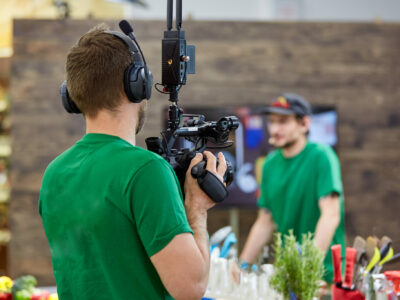 Behind the scenes of movie shooting or video production and film crew team with camera equipment at outdoor location
